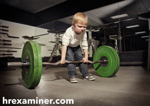 photo of boy struggling to lift heavy barbell or weight on hrexaminer