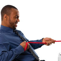 man having tug-o-war with computer