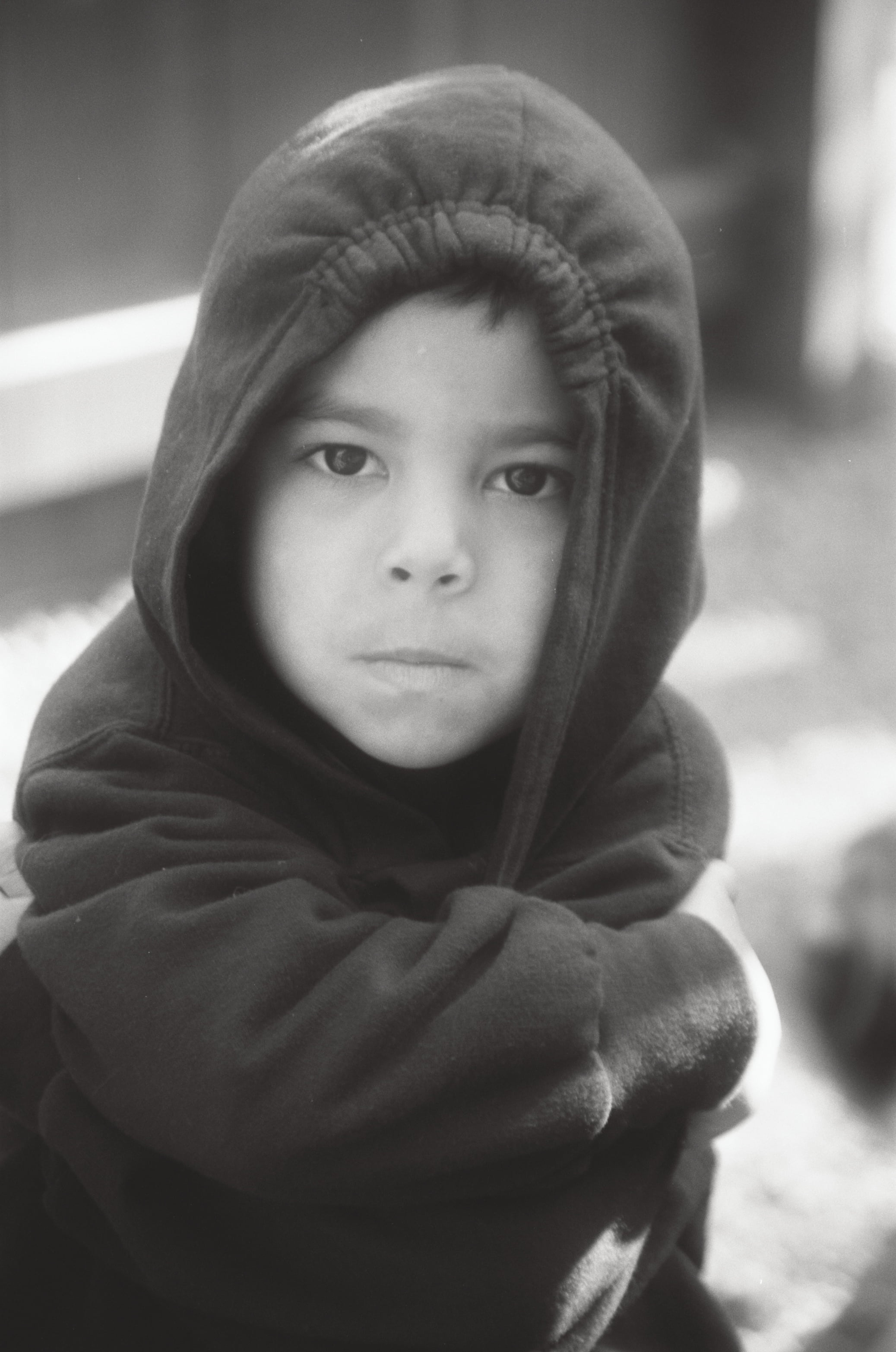 black and white photo of little boy in a hooded sweatshirt