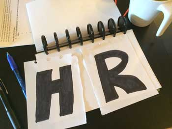 Photo of piece of torn paper with letters showing HR torn down middle on HRExaminer.com