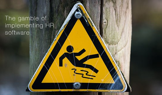 "photo of warning sign ""slippery when wet"" on HRExaminer.com feature image v7.09 The gamble of implementing HR software"