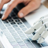 Human and robot hand type on same keyboard - 2020-08-25 HR Examiner article John Sumser The Human Machine Learning Partnership photo img AdobeStock_205145568 sq 200px.jpg